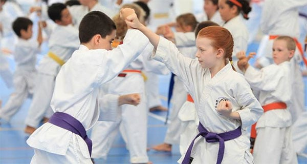 Karate students practicing upper blocks